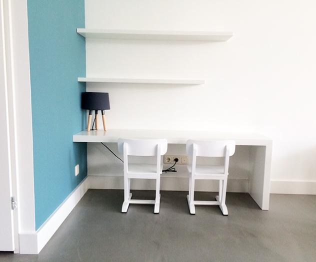 Kinderhoekje; planken en tafel tegen de wand, en twee stoeltjes